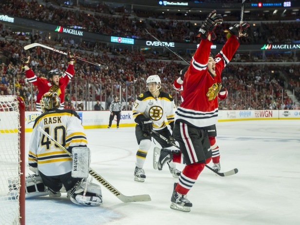 The thrill of victory; the agony of defeat: Andrew Shaw of the Chicago Blackhawks (right) celebrates after the game-winning goal goes in. Boston Bruins goaltender Tuukka Rask looks back toward the puck that's now in his net